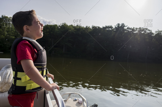 Side view of boy wearing life jacket screaming on boat in lake at forest