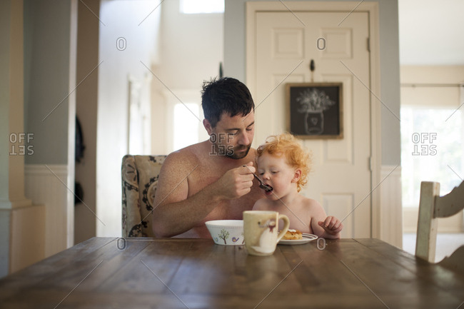 Shirtless father feeding breakfast to cute son at dining table