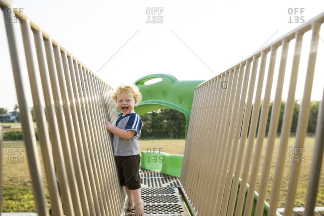 Portrait of cute cheerful baby boy playing on outdoor play equipment at playground