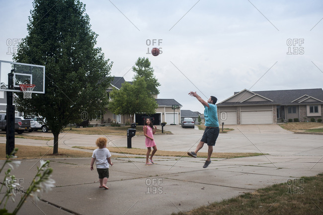 Father playing basketball with children on court