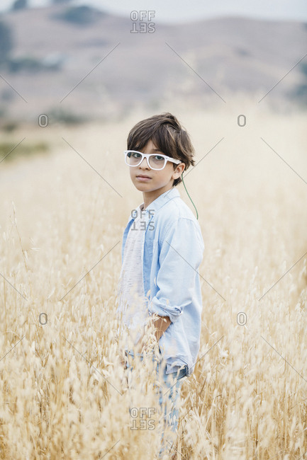Portrait of serious boy wearing eyeglasses while standing on grassy field