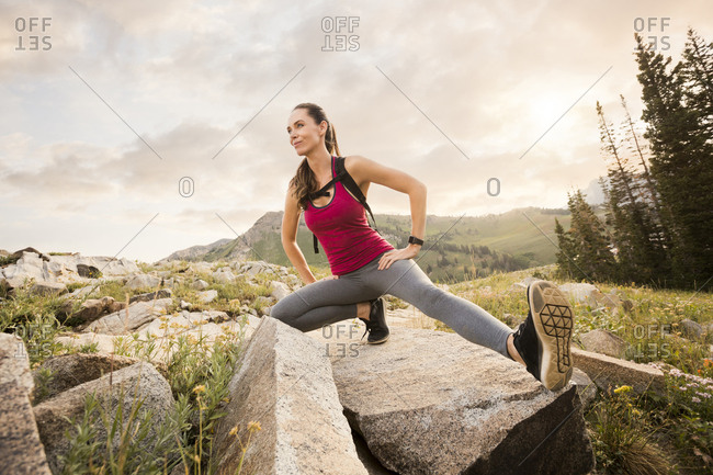 Low angle view of confident female hiker exercising on rocks against cloudy sky in forest