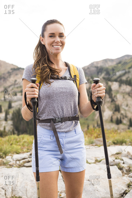 Portrait of smiling female hiker with hiking poles standing on mountain against clear sky in forest