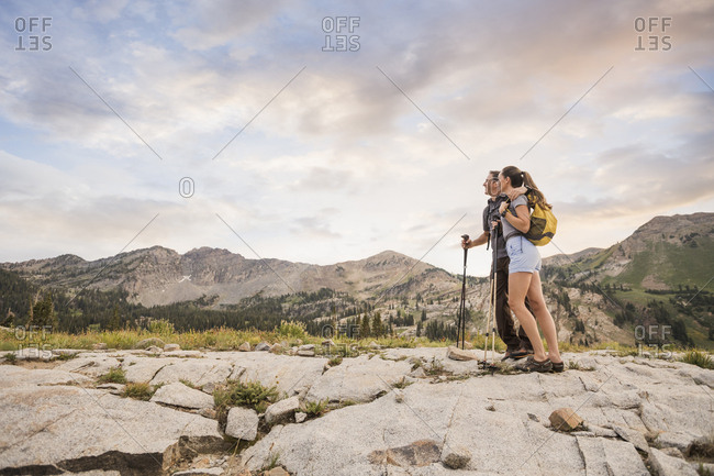 Low angle view of couple looking away while standing on landscape against cloudy sky in forest
