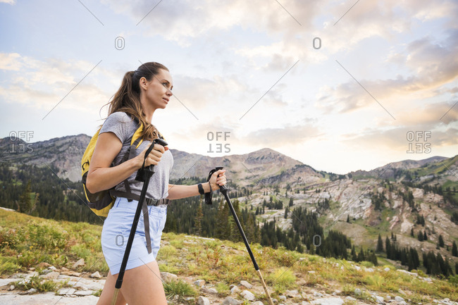 Low angle view of female hiker with hiking poles walking on mountain against sky