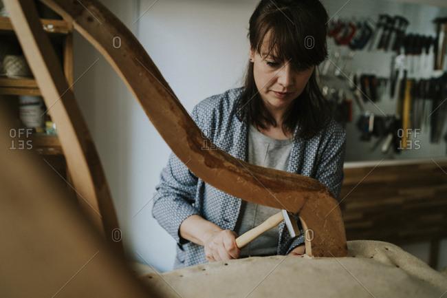 Confident female upholsterer upholstering wooden chair in workshop