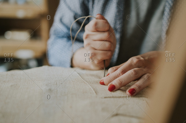 Midsection of female upholsterer stitching fabric on chair in workshop