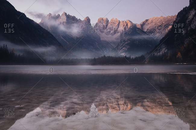 Scenic view of mountains reflecting on calm lake against sky during sunrise