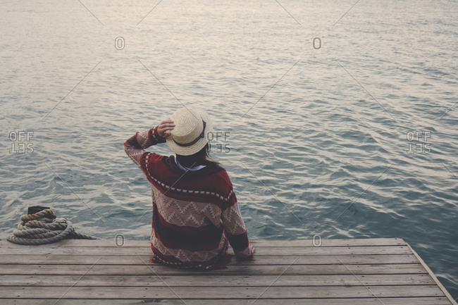 Rear view of woman wearing hat looking at lake while sitting on wooden pier during sunset