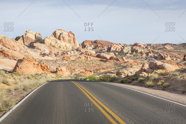 Diminishing perspective of empty road amidst rock formations against sky during sunny day