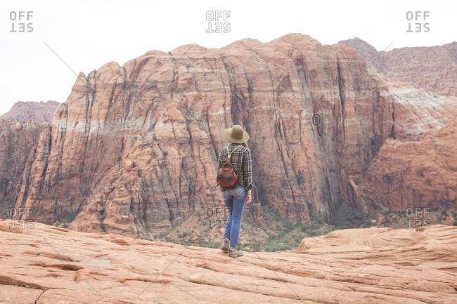 Rear view of woman with backpack looking at mountains while standing on rock formation against sky in Snow Canyon State Park