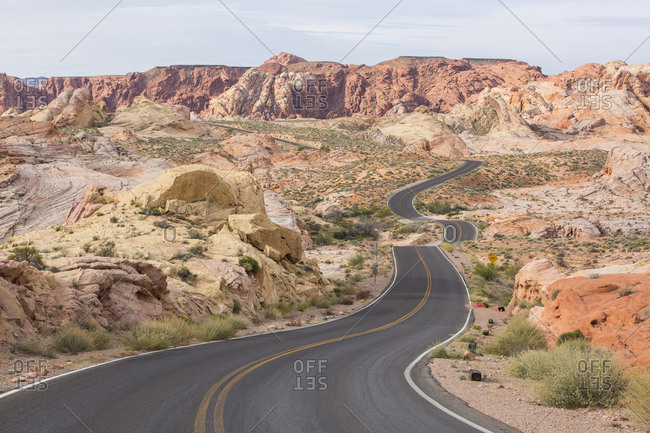 Diminishing perspective of empty road amidst rock formations against sky