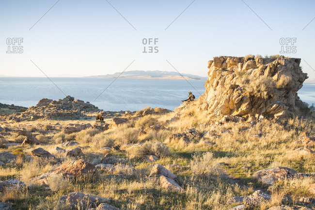 Mid distance view of woman looking at sea while sitting on rock formation against sky