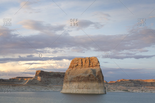 Scenic view of Lake Powell by cliffs against cloudy sky during sunset