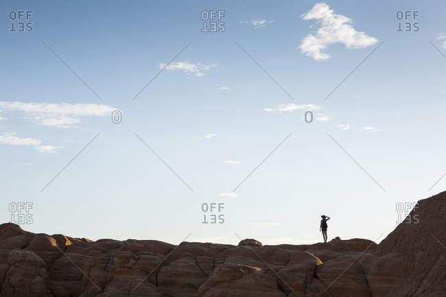 Low angle view of silhouette woman standing on mountain against sky