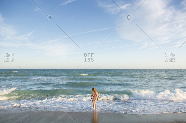 Rear view of woman standing on shore at beach against sky during sunset