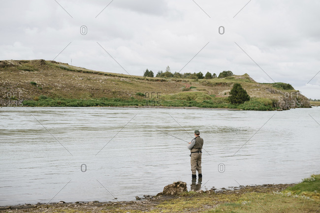 Side view of man fishing while standing in lake against cloudy sky