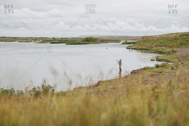 High angle view of man fishing in lake against cloudy sky