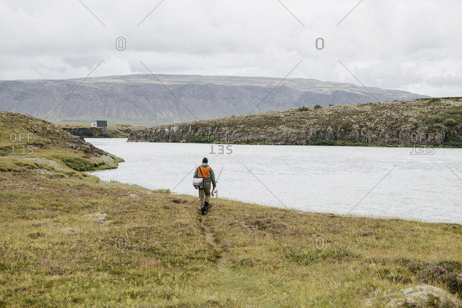 Rear view of man with fishing rod and bag walking on grassy field towards lake against cloudy sky