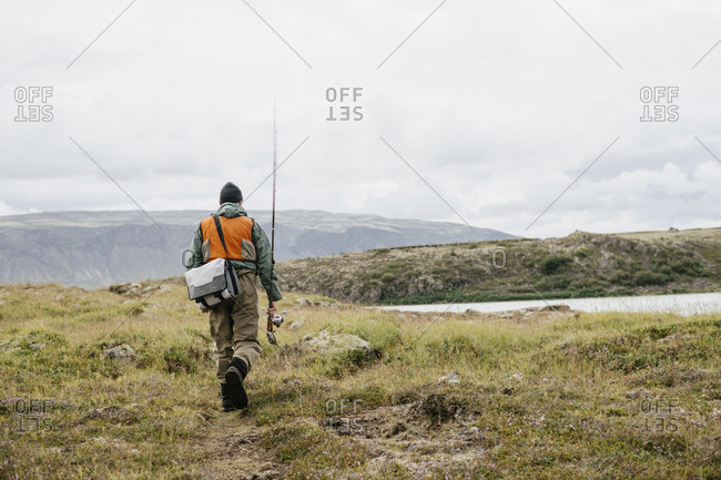 Rear view of man with fishing rod and bag walking on grassy field against cloudy sky