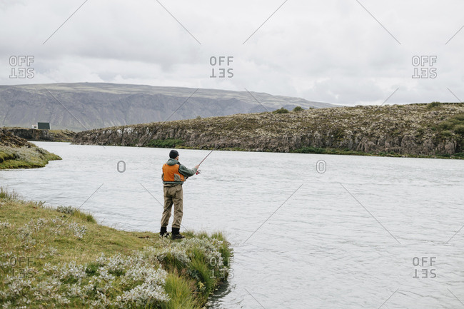 Rear view of man fishing in lake while standing on grassy field against cloudy sky