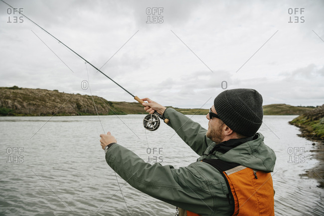 Side view of man fishing in lake while standing against cloudy sky at Iceland