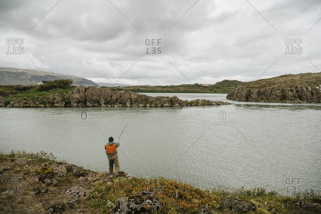 Rear view of man fishing in lake against cloudscape at Iceland