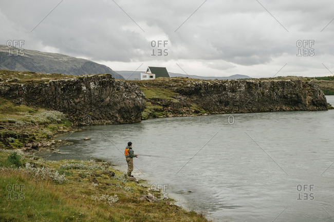 Side view of man fishing in lake while standing against cloudscape at Iceland