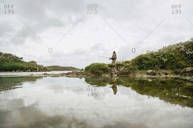 Water surface image of man fishing in lake while standing against cloudy sky at Iceland