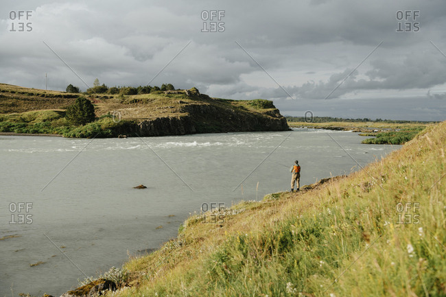 Rear view of man fishing in lake against cloudy sky at Iceland during sunny day