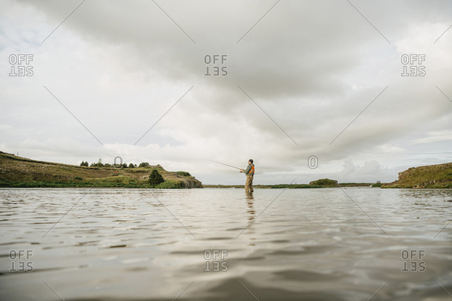 Water surface image of man fishing while standing in lake against cloudy sky at Iceland
