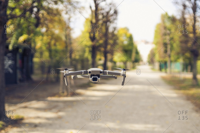 Quadcopter flying over road against trees in park