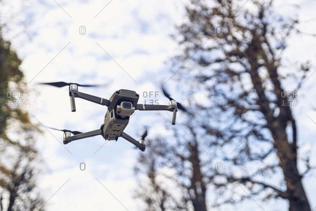 Low angle view of quadcopter flying against trees and cloudy sky