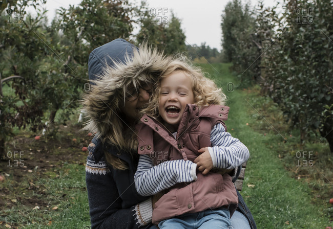 Happy mother with daughter sitting on grassy field in forest