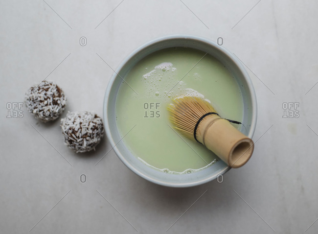 Overhead view of matcha tea with sweet food served on table