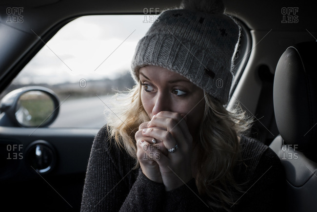Close-up of woman with hands clasped looking away while sitting in car