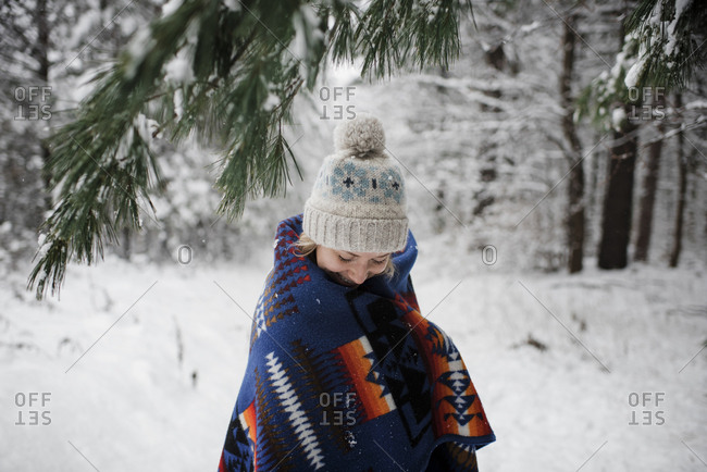 Woman wrapped in blanket standing against trees at forest during winter