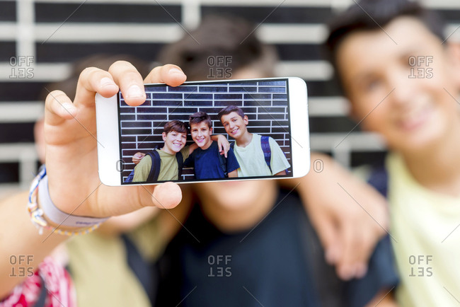 Close-up of smiling friends taking selfie with smart phone while standing against wall