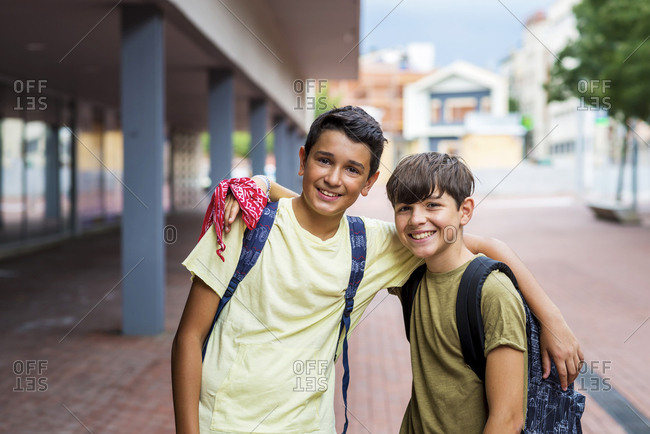 Portrait of smiling friends with arms around standing on footpath against buildings