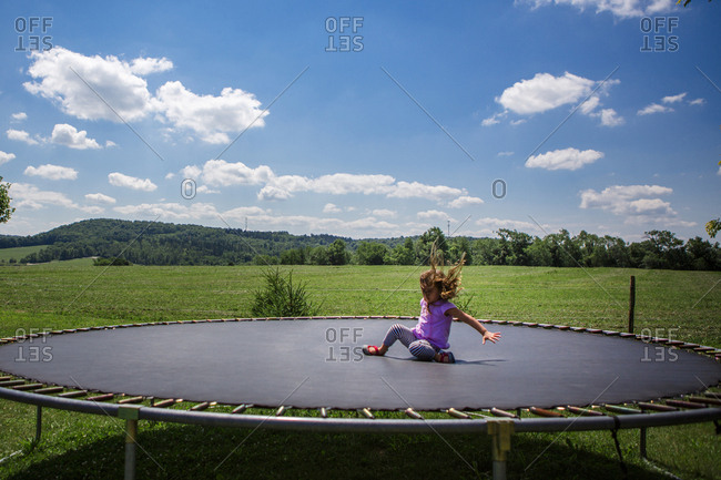 Playful girl jumping on trampoline against blue sky at park during sunny day