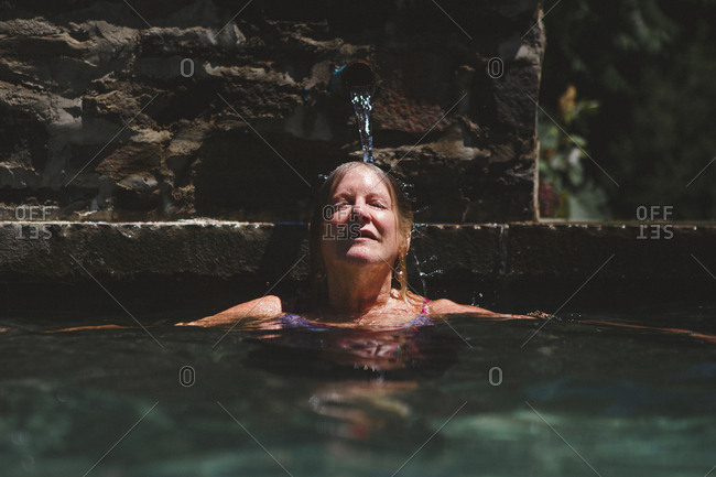 Woman with eyes closed swimming in pool at tourist resort during sunny day