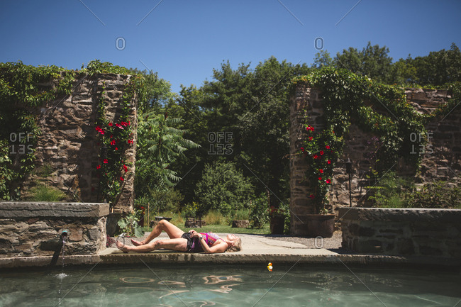 Side view of woman in swimwear lying on poolside at tourist resort against trees during sunny day