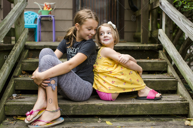 Cute sisters looking at each other while sitting on steps against house in yard