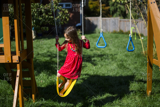 High angle view of playful girl standing on swing at playground during sunny day