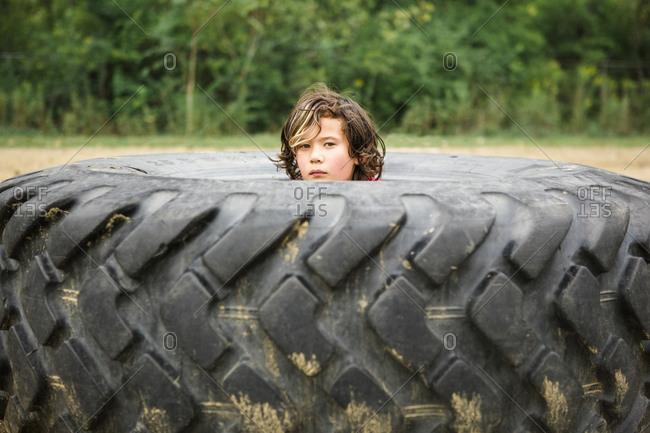 Portrait of cute boy peeking through dirty tire against plants