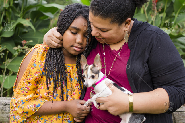 Mother holding Chihuahua embracing daughter while sitting against plants in park