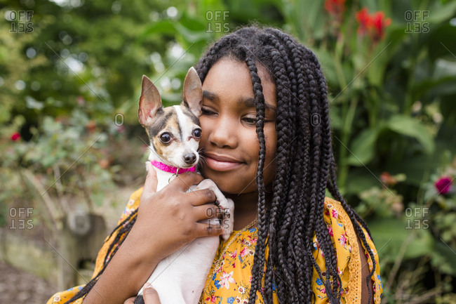 Close-up of smiling girl carrying cute Chihuahua while standing against plants in park