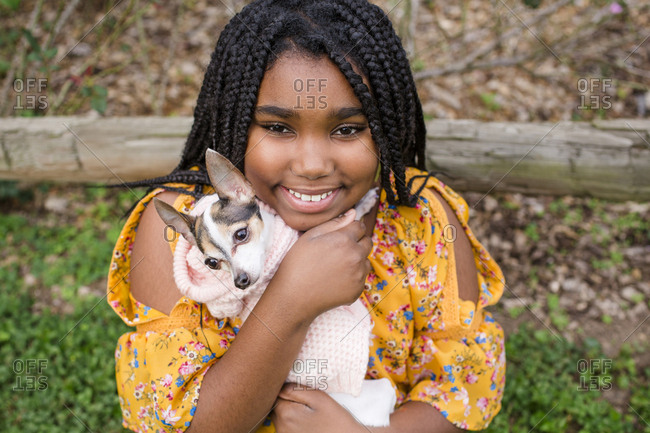 Portrait of smiling girl carrying cute Chihuahua while standing in park