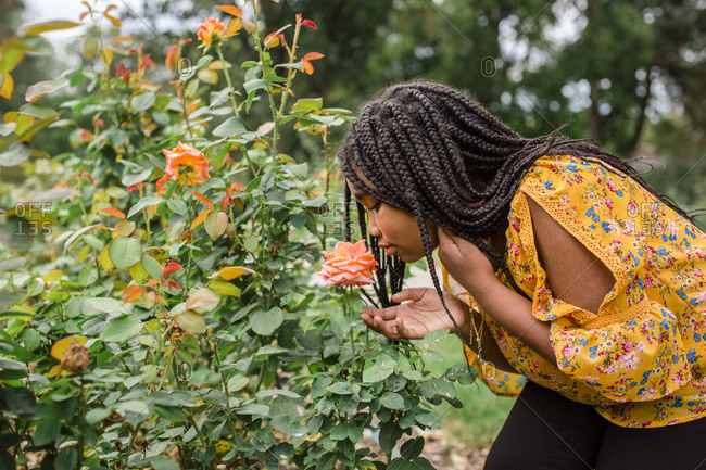 Side view of girl smelling flower while standing in park