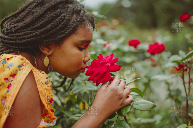 Side view of girl smelling red flower while standing in park